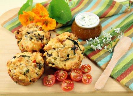 Photo pour Muffins salés frais cuits au four avec tartinade d'herbes et tomates cerises . - image libre de droit