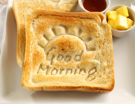 Photo for Slice of toast with Good Morning carved into it with butter and honey. - Royalty Free Image