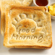 Slice of toast with Good Morning carved into it wi...