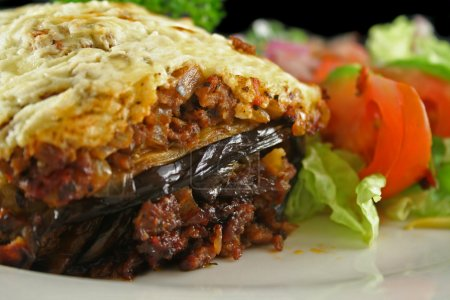 Photo for Lamb moussaka with egg plant cheese and salad. - Royalty Free Image