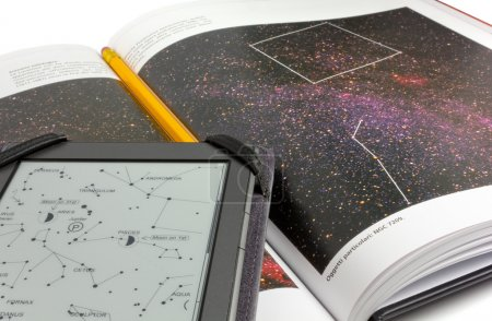 An astronomy atlas with a pencil on it and an e-bo...