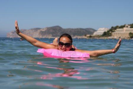 Photo pour Femme heureuse reposante sur un matelas dans la mer - image libre de droit