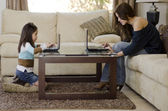 Young mother and daughter using their laptops in the living room