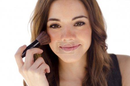 Young beautiful woman applying blush...