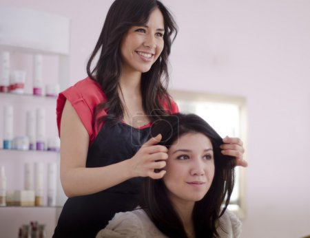Young female hairdresser showing final result to customer