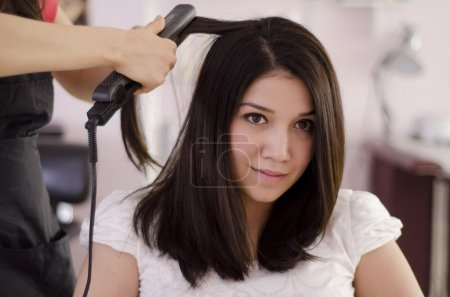 Female hairdresser straightening the hair of a client