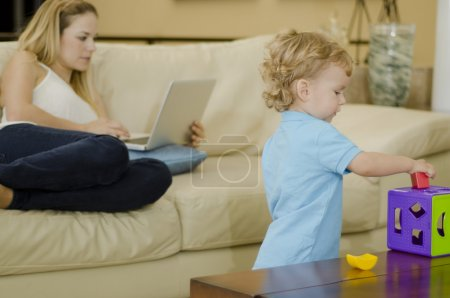 Cute boy playing with a puzzle while mom works