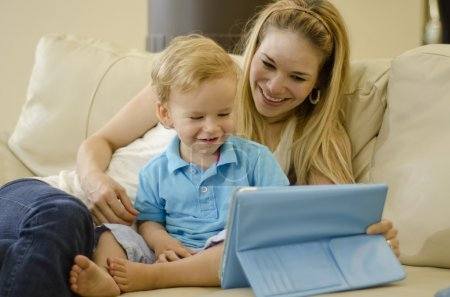 Beautiful young mother playing with her son and a tablet