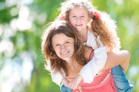 Photo for Beautiful and happy young mother giving piggyback ride to her daughter. Both smiling and looking into the camera. Summer park in background. - Royalty Free Image