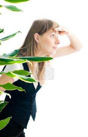 Photo pour Curieuse jeune belle femme d'affaires isolée sur fond blanc regardant hors de l'usine de bureau et espionnant quelqu'un - image libre de droit