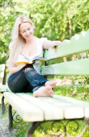 Photo pour Jeune femme assise sur un banc dans un parc, lisant un livre et souriant - image libre de droit
