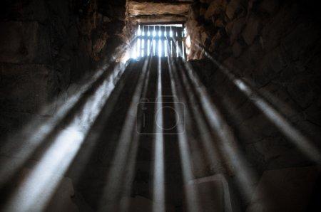 Photo pour Rayons du soleil rayonnant à travers la fenêtre de la prison dans la cellule - image libre de droit