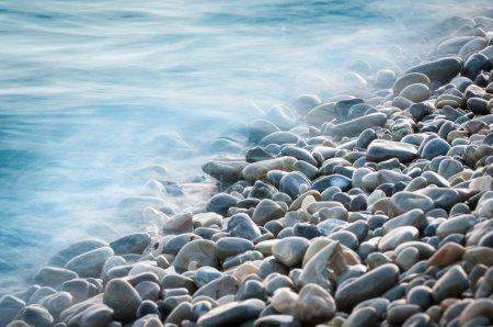 Photo pour Pierres de galets au bord de la mer. soyeux vagues d'une mer bleue de longue exposition. - image libre de droit
