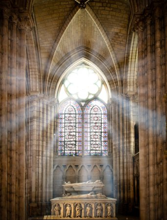 Sun rays beaming through the old stained glass win...