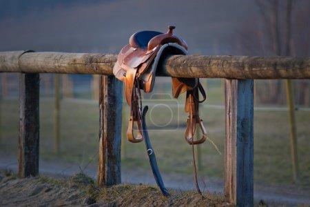 Photo pour Selle Western sur la clôture, la lumière du soleil du soir - image libre de droit
