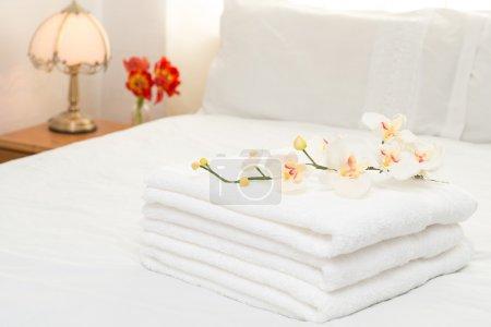 Freshly laundered white fluffy towels in bedroom i...