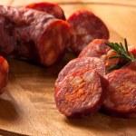 Spanish chorizo sausage with rosemary on rustic bo...