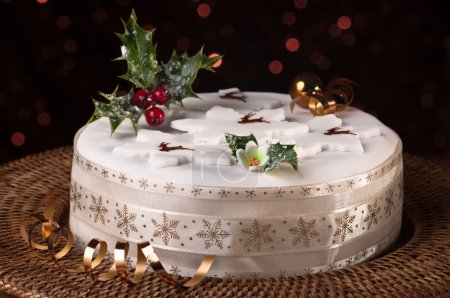 Photo for Christmas fruit cake decorated with holly and berries with sparkly background - Royalty Free Image
