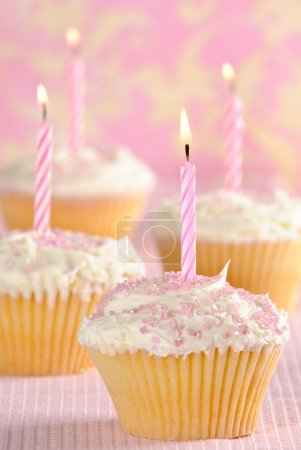 Photo for Party cupcakes with pink striped lit candles - Royalty Free Image