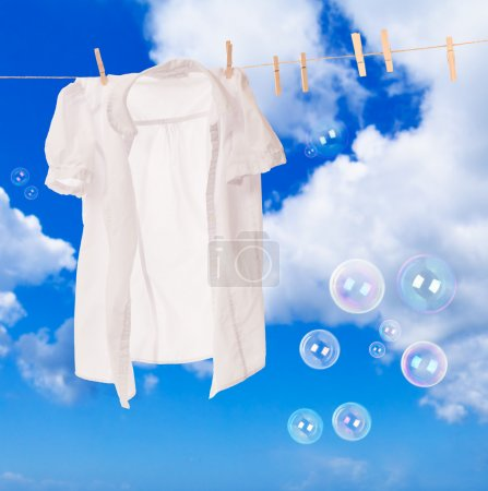 White shirt hanging on washing line with soap bubb...