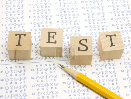 Photo for Wooden blocks spell out TEST on a blue bubble or scantron sheet with a number two yellow pencil. - Royalty Free Image