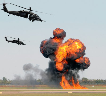 Photo for Helicopters mounting a ground attack with explosions and smoke - Royalty Free Image