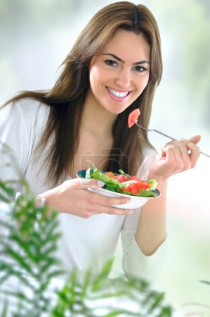 Photo for Young beautiful woman eating salad - Royalty Free Image
