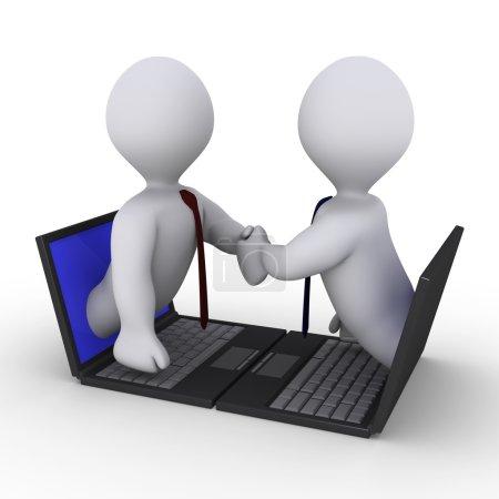 Photo pour Deux hommes d'affaires serrent la main à travers les écrans d'ordinateurs portables - image libre de droit