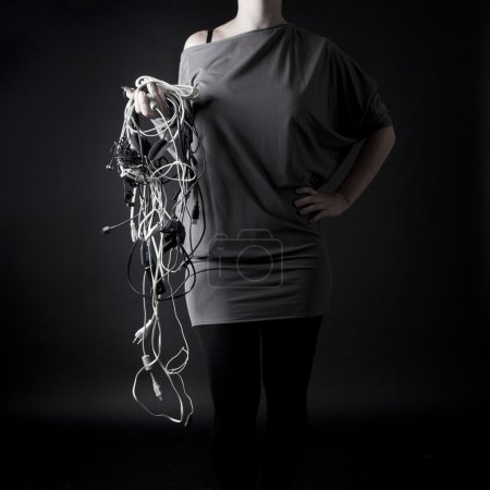 A young woman with the bunch of wires in the hand...