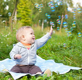 Boy sitting on green grass outdor playing with soap bubbles