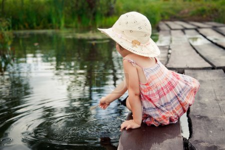 Adorable small girl sitting on the wooden bridge and thoughtfully looking on the river