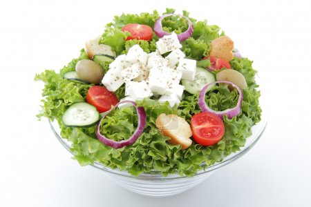 Mixed salad with feta and tomatoes on white background