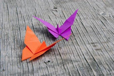 Foto de Rosa y naranja origami mariposas sobre fondo de madera vintage - Imagen libre de derechos