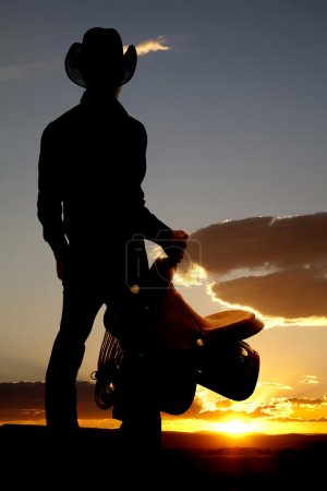 Cowboy holding saddle silhouette