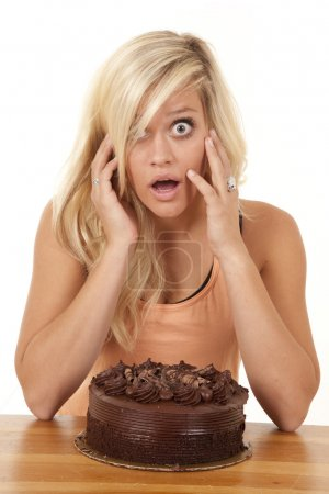 Woman wtih cake and shocked expression