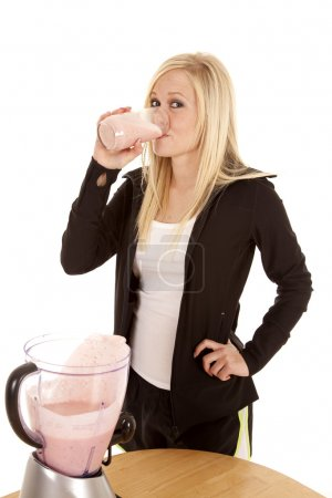 Woman drinking smoothie by table