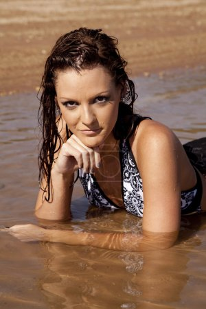 Photo for A woman laying in the water with a serious expression on her face. - Royalty Free Image