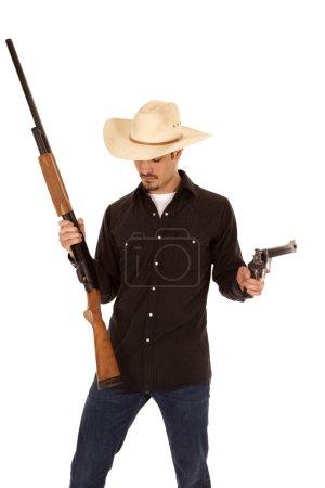 Photo pour Un cow-boy tient deux canons et regardant vers le bas. - image libre de droit