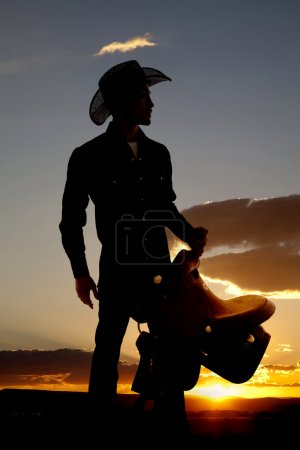 Cowboy silhouette with saddle