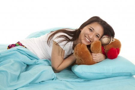 Woman in bed with bear laying on