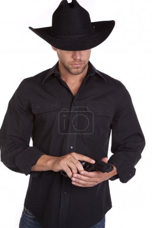 Photo for A cowboy in his black hat looking down at the gun in his hand. - Royalty Free Image