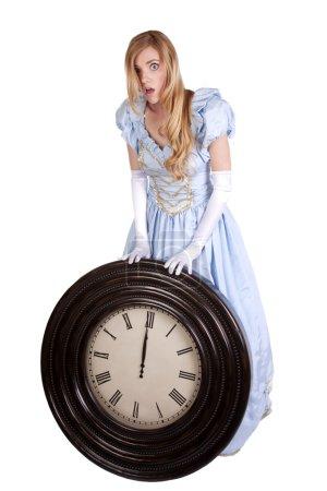 Photo pour Une femme vêtue d'une robe de Cendrillon, brandissant une grande horloge peur de savoir qu'il est minuit. - image libre de droit