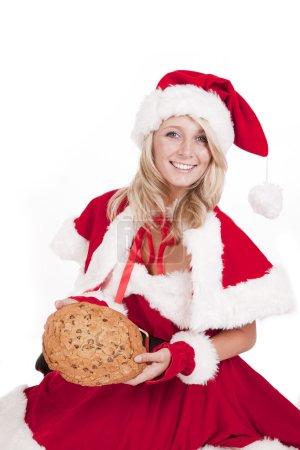Photo pour Une femme habillée comme le Père Noël avec un gros cookie . - image libre de droit