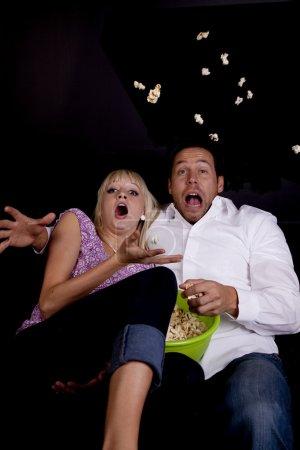 Photo pour Un couple regardant un film d'horreur et ça leur faisait tellement peur qu'ils ont jeté le pop-corn . - image libre de droit