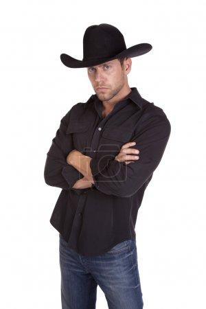 Photo pour Un homme dans un chapeau de cowboy noir montrant qu'il signifie entreprise par son expression sérieuse. - image libre de droit