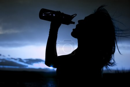 Silhouette of a woman with a water bottle close up