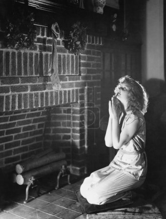 Portrait of teenage girl praying at hearth with Christmas stocking