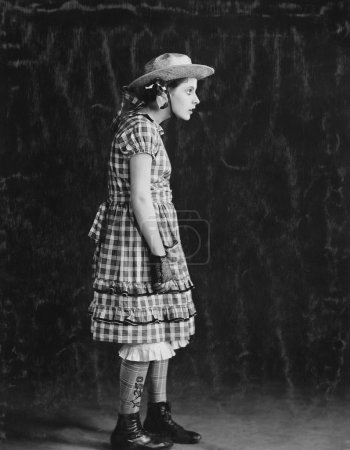 Portrait of girl in plaid dress and straw hat