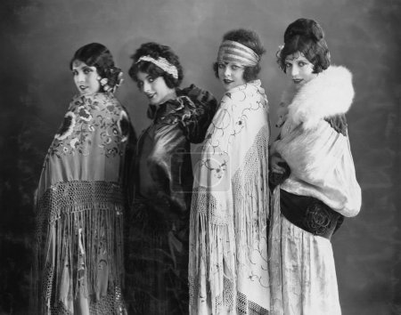 Portrait of four young women posing in shawls