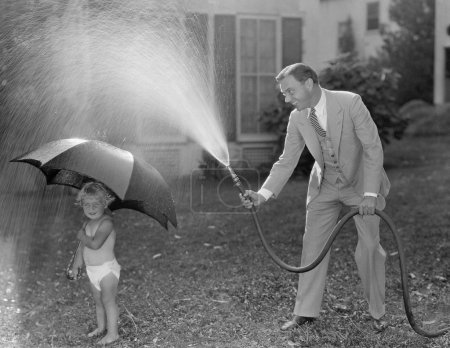 Toddler and dad playing with hose in yard
